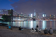 People gather in sit on the rocky beach in Brooklyn Bridge Park to watch the Brooklyn Bridge and the Manhattan sklyine light up as sun sets and night falls in New York City.