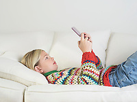Girl lying on sofa Playing Handheld Video Game side view