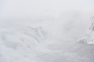 The waterfall Gullfoss of the river Hvita with ice formations in a snowstorm in the winter, vally Haukadalur, Iceland