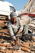 A Syrian refugee chops up firewood at the displaced persons camp in Atmeh, Syria.