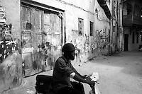 Man riding a scooter in Stone Town, Zanzibar, Tanzania