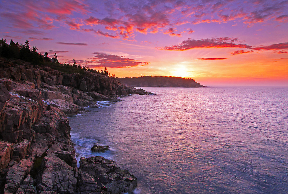 Maine Acadia National Park sunrise coastal photography images are available as museum quality photography prints, canvas prints, acrylic prints, wood prints or metal prints. Prints may be framed and matted to the individual liking and room decor needs:<br /> <br /> http://juergen-roth.pixels.com/featured/atlantic-glow-juergen-roth.html<br /> <br /> Beautiful sunrise seacoast photography showing a spectacular vista across the beautiful cliffs of the Maine rocky coastal shoreline in Acadia National Park. <br /> Acadia NP is a National Park located in the U.S. state of Maine. It reserves much of Mount Desert Island, and associated smaller islands, off the Atlantic coast. The park is one of the most visited wildlife areas in the United States and a paradise for every photographer and outdoor enthusiast. The park loop road provides easy access to many of the iconic photography subjects, such as Monument Cove, Sand Beach, Jordan Pond and the Bubbles, Otter Cliff to name only a few. The carriage roads and hiking trails provide further access to more remote locations where the park continues to inspire and unfolds its full magic. It is a heaven for macro, seascape, and landscape photography that makes for great wall art decoration. Especially sunrise and the light of the golden hours paint the sky in beautiful blue and orange and bring out the beauty of the pink granite rocks.<br /> <br /> Good light and happy photo making! <br /> <br /> My best, <br /> <br /> Juergen <br /> Website: www.RothGalleries.com<br /> Twitter: @NatureFineArt<br /> Facebook: https://www.facebook.com/naturefineart<br /> Instagram: https://www.instagram.com/rothgalleries