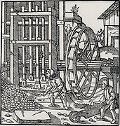 Overshot water wheel turning the cam-shaft of a stamping mill  being used to turn the crush ore to begin the process of extracting metal from the ore won from a mine.  From 'De re metallica', by Agricola, pseudonym of Georg Bauer (Basle, 1556).  Woodcut