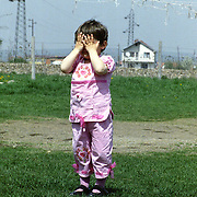 A child in a field outside a school in the outskirts of Pristina, Kosovo.  Schooling is provided with the aid of ngo aid.