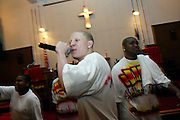 Tykym, 18, (centre) and Michael, 17, (right) members of the Hells Most Wanted, a Christian Hip Hop group, are singing while a young member of the Hip Hop Church Choir, Ivan Bryan, 12, (left) is dancing in front of the altar, during a Mass Service at the Hip Hop Church in Harlem, New York, NY., on Thursday, June 29, 2006. A new growing phenomenon in the United States, and in particular in its most multiethnic city, New York, the Hip Hop Church is the meeting point between Hip Hop and Christianity, a place where ëGodí is worshipped not according to religious dogmatisms and rules, but where the ëHoly Spirití is celebrated by the community through young, unique, passionate Hip Hop lyrics. Its mission is to present the Christian Gospel in a setting that appeals to both, those individuals who are confessed Christians, as well as those who are not regularly attending traditional Services, while helping many youngsters from underprivileged neighbourhoods to feel part of a community, to make them feel loved and to help them not to give up when problems arise. The Hip Hop Church is not only forward-thinking but it also has an important impact where life at times can be difficult and deceiving, and where young people can be easily influenced for the worst purposes. At the Hip Hop Church, members are encouraged to sing, dance and express themselves in any way that the ëSpirit of Godí moves them. Honours to students who have overcome adversity, community leaders, church leaders and some of the unsung pioneers of Hip Hop are common at this Church. Here, Hip Hop is the culture, while Jesus is the centre. Services are being mainly in Harlem, where many African Americans live; although the Hip Hop Church is not exclusive and people from any ethnic group are happily accepted and involved with as much enthusiasm. Rev. Ferguson, one of its pioneer founders, has developed ëHip-Hop Homileticsí, a preaching and worship technique designed to reach the children in their language and highlig