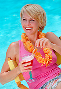Smiling woman, 30-35, holding tropical drink with umbrella garnish, pool background.
