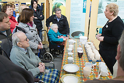 Visually impaired people with carers on outing to Denby Pottery. Listening to a talk.
