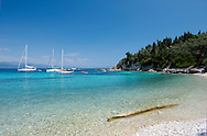Sailing yachts off Marmari Beach on the east coast of Paxos, The Ionian Islands, The Greek Islands, Greece, Europe