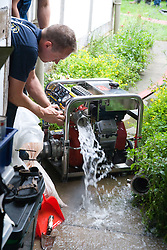 Member of the fire rescue service using a high volume pump (HVP) to drain away flood water after torrential rain caused the river Severn to bust its banks and flooded the Tewkesbury area; Gloucestershire; July 2007,