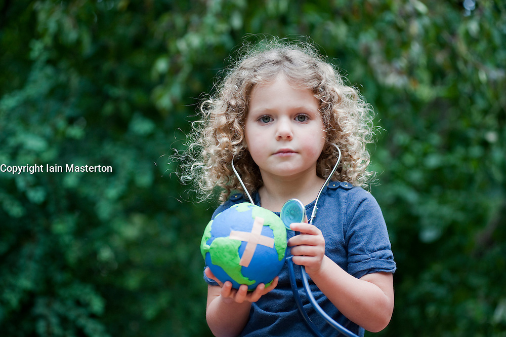 Young girl holding model of planet Earth with a Band-aid attached and checking its health with a stethoscope