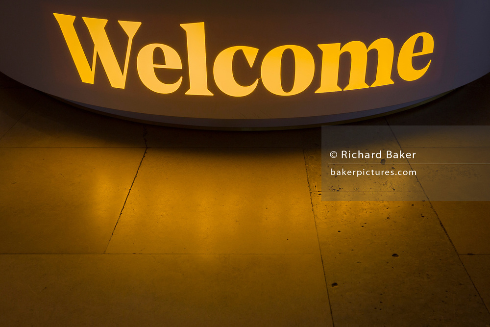The yellow light from a Welcome sign is reflected on the floor of the Festival Hall on London's Southbank, on 5th October, 2017, in London, England.