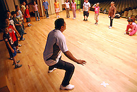 "USA, Chicago, July 2nd - 23rd, 2009.  Professional instructor Ruben Pachas, who is Peruvian, at work with his students. For almost 20 years, Polo Garcia, a professional dance teacher from ""America Baila,"" has been giving traditional South American dance lessons at various Pilsen and Little Village schools, including Maria Saucedo Scholastic Academy, whose turn-of-the-century auditorium is featured here. Garcia, who is Mexican, does the research for these dances in-person, makes the costumes himself, and provides free summer classes. He works with Claudio Rabadan, a former Saucedo student. Photographs for HOY by Jay Dunn."