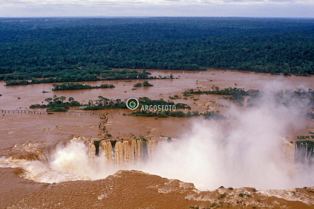 Foz do Iguacu, Parana, Brasil..As Cataratas do Iguacu (espanhol: Cataratas del Iguazu) sao uma reuniao de quedas no Rio Iguacu (Bacia do Parana), localizam-se dentro do Parque Nacional do Iguacu no Brasil e no Parque Nacional Iguazu na Argentina que, somados, correspondem a 250 mil hectares de floresta protegida. Os parques tanto brasileiro como argentino passaram a ser considerados Patrimonio da Humanidade em 1984 e 1986, respectivamente. Historicamente, as Cataratas do Iguacu foram descobertas em 1542 por Dom Alvar Nunez Cabeza de Vaca. O nome Iguacu vem das palavras da língua guarani y (agua) e guacu (grande)./ Iguazu Falls (Spanish: Cataratas del Iguazu are waterfalls of the Iguazu River located on the border of the Brazilian state of Parana (in the Southern Region) and the Argentine province of Misiones. The Falls are shared by the Iguazu National Park (Argentina) and Iguacu National Park (Brazil). These parks were designated UNESCO World Heritage Sites in 1984 and 1986 respectively. The name Iguazu comes from the Guarani words y (water) and guasu (big). The first European to find the falls was the Spanish Conquistador Alvar Nunez Cabeza de Vaca..Foto © Marcos Issa/Argosfoto