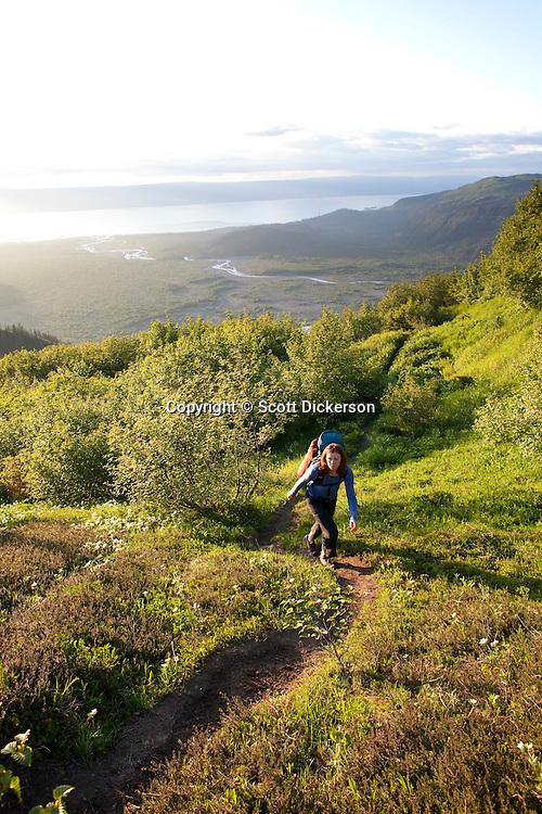 Stephanie Haynes hiking on the Alpine Ridge trail in Kachemak Bay State Park, near Homer, Alaska. Grewingk River drains the Grewingk Glacier lake into Kachemak Bay in the valley below.