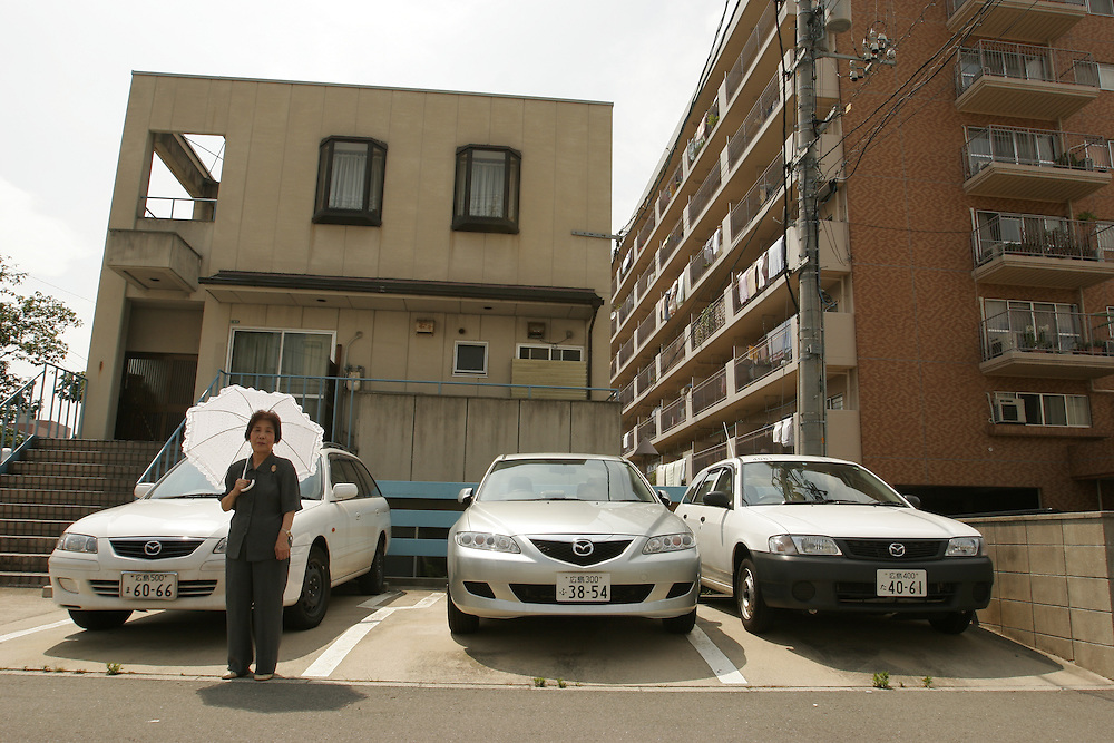 Hiroshima  Ms. Watanabe stands inthe parking lot  infront of an  apartment  building where her  house  once stood it was completely destroyed by the  atomic Bomb,