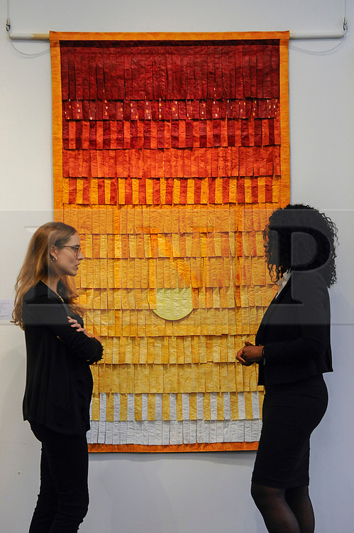 "© Licensed to London News Pictures. 12/05/2017. London, UK.   Staff members stand in front of ""Composition No. 25 (Soleil)"", 2015, by Abdoulaye Konaté (Mali) (Est. GBP 10-15k) at the preview for the first sale dedicated to Modern and Contemporary African Art at Sotheby's New Bond Street.  The sale features over 115 artworks by over 60 different artists from 14 countries across the continent. Photo credit : Stephen Chung/LNP"