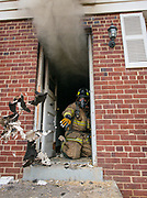 A firefighter throws debris out the door of a burning house.