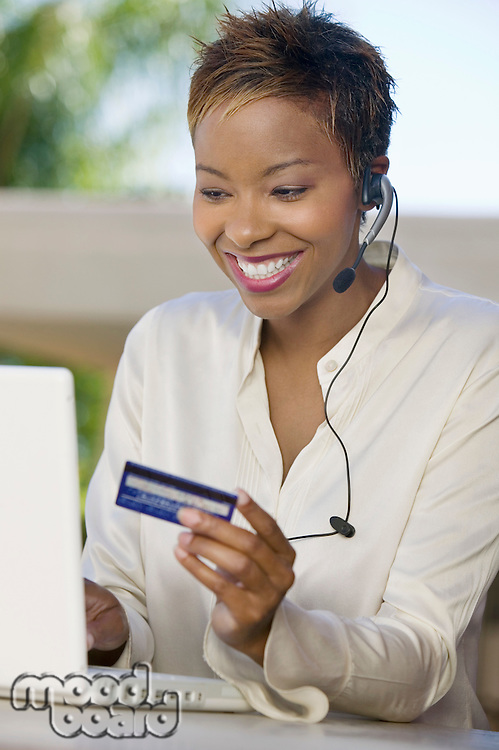 Woman with laptop on patio Using Credit Card to make online purchase