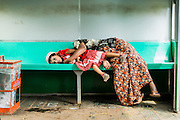 15 JUNE 2013 - YANGON, MYANMAR:   A woman and her daughter sleep on the Yangon Circular Train. Yangon Circular Railway is the local commuter rail network that serves the Yangon metropolitan area. Operated by Myanmar Railways, the 45.9-kilometre (28.5 mi) 39-station loop system connects satellite towns and suburban areas to the city. The railway has about 200 coaches, runs 20 times and sells 100,000 to 150,000 tickets daily. The loop, which takes about three hours to complete, is a popular for tourists to see a cross section of life in Yangon. The trains from 3:45 am to 10:15 pm daily. The cost of a ticket for a distance of 15 miles is ten kyats (~nine US cents), and that for over 15 miles is twenty kyats (~18 US cents). Foreigners pay 1 USD (Kyat not accepted), regardless of the length of the journey.     PHOTO BY JACK KURTZ