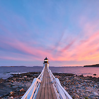 New England photography of Marshall Point Light with its iconic wooden walkway at sunset. This beautiful New England lighthouse is located Port Clyde in Maine and marks the entrance to Port Clyde harbor.<br />