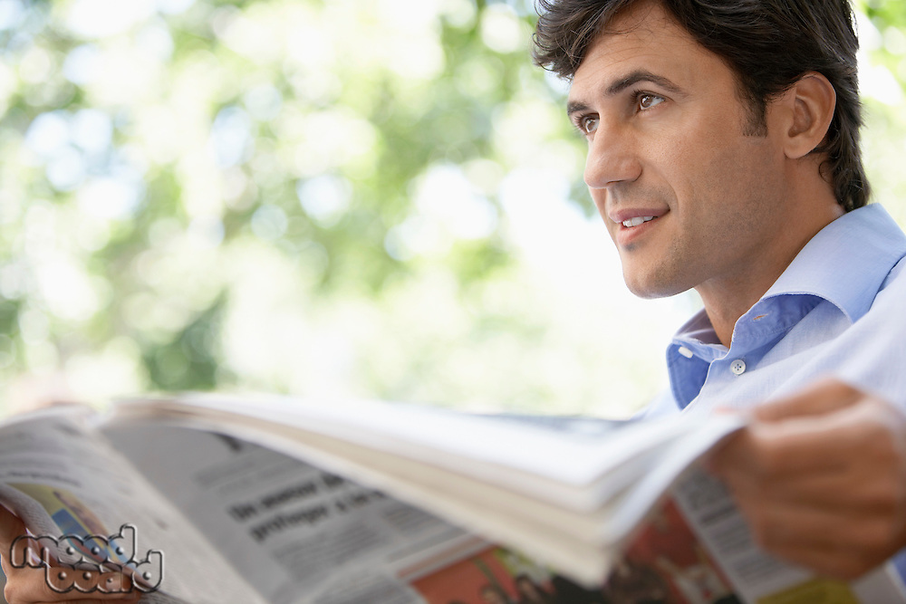 Mid-adult man reading newspaper outdoors close-up