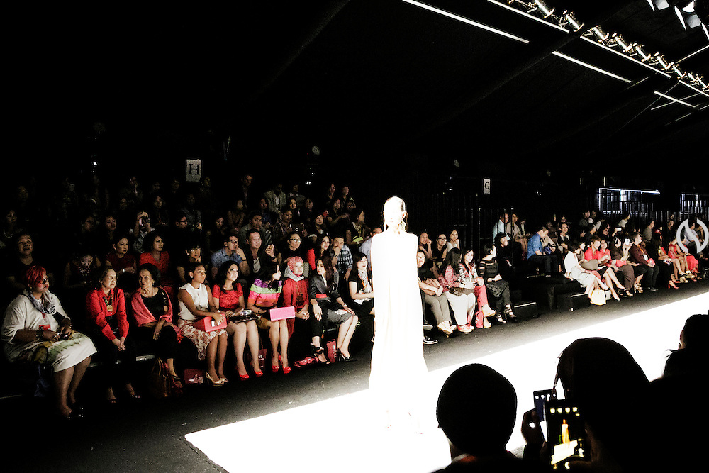 JAKARTA; TUESDAY, NOVEMBER 4, 2014; INDONESIA ECONOMIC RISING: Spectators from upper middle class pay attention to model as she presents an attire at Jakarta Fashion Week, in Jakarta, Indonesia, on Tuesday, November 4, 2014. According to Asian Development Bank's 2014 report, Indonesia economy growth potential is in creative industry after for years relies heavily on natural resources such as mineral mining and palm oil. By the presidency of Joko Widodo, as a product of the third people election after the People Power Revolution in 1998, Indonesia is more confident in the economy growth and optimistic to become equal in quality to Brazil and China's economy growth. The emerging of Indonesia economy for the last one and a half decade after the end of Suharto's Dictatorship has been in significant way, the per capita growth has reached 400% under Susilo Bambang Yudhoyono presidency. Indonesia is home for 74 million of middle class as estimated by Boston Consulting Group, and  will double in 2020.