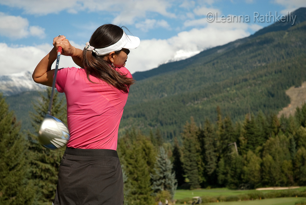 Female golfer Mei Liu tees off the 16th hole on the Whistler Golf Course, Whistler, BC Canada.