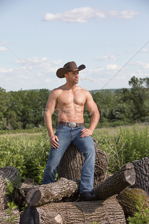 hot cowboy sitting on cut wood with straw in his mouth