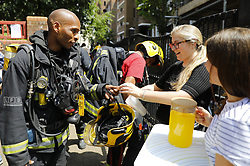 © Licensed to London News Pictures. 14/06/2017. London, UK. Volunteers give biscuits and drinks to firefighters as the Grenfell Tower fire still is not under control 13 hours after the fire broke in west London on 14 June 2017. Photo credit: Tolga Akmen/LNP