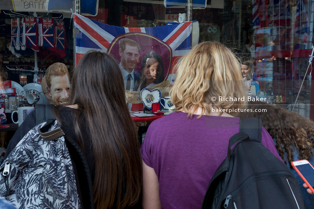 Royal faces of Prince Harry and Meghan Markle stare out towards a passing group of tourists as the royal town of Windsor gets ready for the royal wedding between Harry and his American fiance, on 14th May 2018, in London, England. (Photo by Richard Baker / In Pictures via Getty Images)