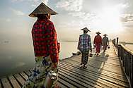 Early morning commute to work across the U Bein bridge near Mandalay, Myanmar.  It is the oldest and longest teak wood bridge in the world.