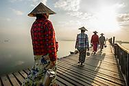 Early morning commute to work across the U Bein bridge near Mandalay, Myanmar.  It is the oldest and longest teak wood bridge in the world.
