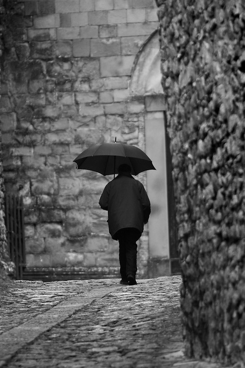 Black and white photograph og man with umbrella in Italy