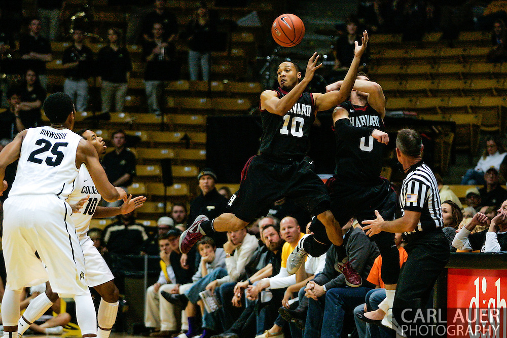 November 24th, 2013:  Harvard Crimson senior guard Brandyn Curry (10) and senior guard Laurent Rivard (0) jump out of bounds to attempt to save the ball in the first half of action in the NCAA Basketball game between the Harvard Crimson and the University of Colorado Buffaloes at the Coors Events Center in Boulder, Colorado