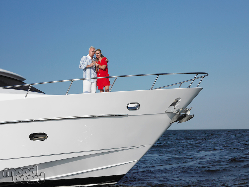 Middle-aged couple standing in bow of yacht