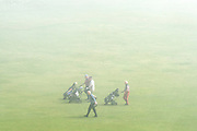 © Licensed to London News Pictures. 14/04/2015. Seaford, UK. Golfers carry on their game in the mist.  People in the early morning sea mist and sunshine in Seaford today 14th April 2015. Today is expected to be a very warm day across Britain. . . Photo credit : Stephen Simpson/LNP