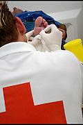 Nederland, Nijmegen, 15-7-2003..Vrijwilliger van het rode kruis prikt blaren bij een vierdaagse loper. 4daagse, 4-daagse. Wandelsport, voeten, blaar. huid...Foto: Flip Franssen