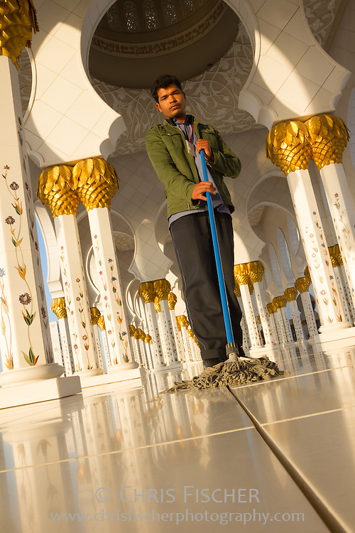 Migrant worker from India mopping floors at the Sheikh Zayed Grand Mosque in Abu Dhabi, UAE.