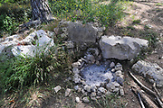 burnt out campfire in a fire pit. stones in a circle around the fire is to prevent the fire from spreading
