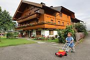 Zillertal, Tyrol, Austria Boy of three palys infront of a chalet