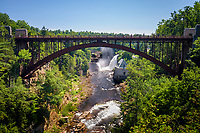 People walk across the Route 9 iron road  bridge over the Ausable River Chasm, New York.
