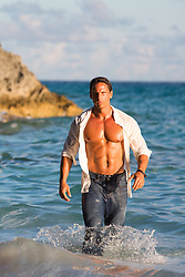 muscular man with an open shirt in the ocean