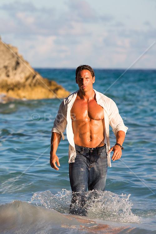 muscular man with an open shirt in the ocean