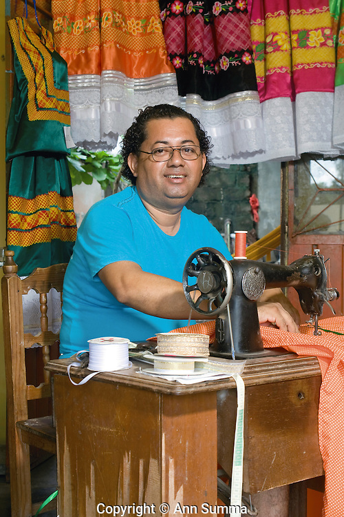 Juchitan, Mexico:   An example of the finely embroided Tejuana clothing of the Isthmus region of Mexico, as displayed in the shop of Muxe (transvestite) seamstress, Eduardo Orozco. Muxes are very common, and accepted, in this Southern Oaxacan region, which claims to not discriminate against gays. The matriarchal society is still driven by women but in flux in the machismo culture of Mexico. Sept. 13, 2008. (photo: Ann Summa).