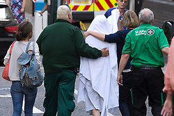 © London News Pictures. 09/08/2013. London, UK. Katie Gee covered in a white sheet being taken into Chelsea and Westminster Hospital after arriving back in the UK. Katie Gee and her friend Kirstie Trup were victims of an acid attack while working as charity volunteers in in Zanzibar. Photo credit : Ben Cawthra/LNP