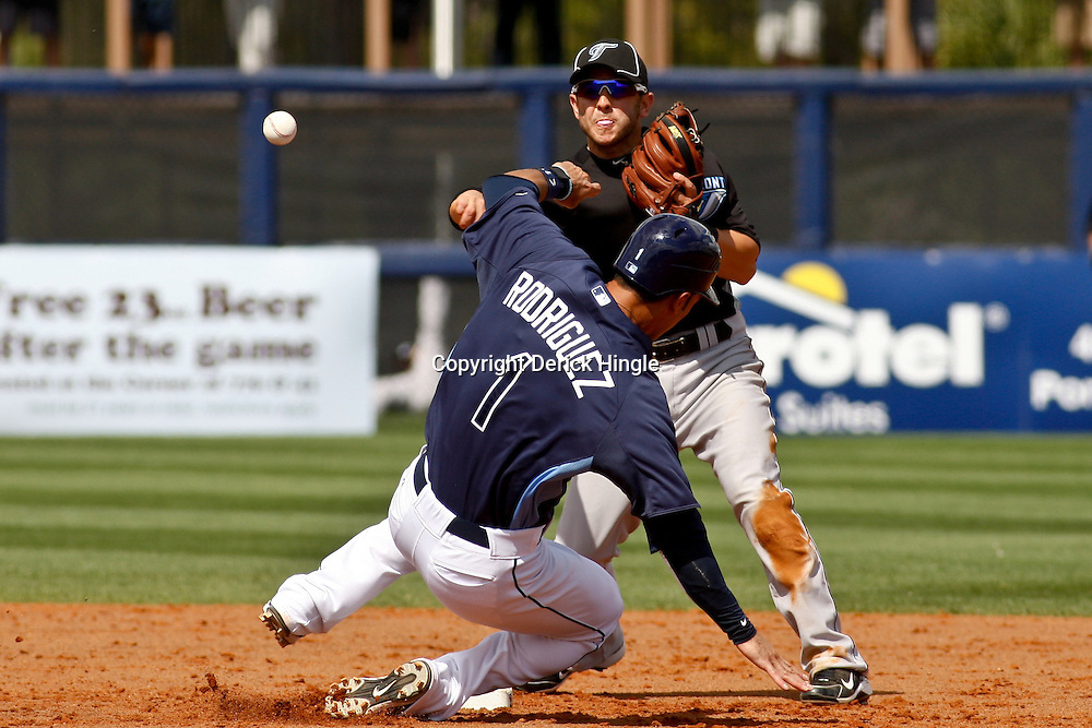 March 8, 2011; Port Charlotte, FL, USA; Toronto Blue Jays second baseman Jonathan Diaz (68) throws as Tampa Bay Rays second baseman Sean Rodriguez (1) slides into second base during a spring training exhibition game at Charlotte Sports Park.   Mandatory Credit: Derick E. Hingle