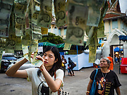 21 NOVEMBER 2015 - BANGKOK, THAILAND: A woman staples a 20Baht note (about $0.60 US) to a chain of 20Baht notes all meant as donations to the temple at the Wat Saket temple fair. Wat Saket is on a man-made hill in the historic section of Bangkok. The temple has golden spire that is 260 feet high which was the highest point in Bangkok for more than 100 years. The temple construction began in the 1800s in the reign of King Rama III and was completed in the reign of King Rama IV. The annual temple fair is held on the 12th lunar month, for nine days around the November full moon. During the fair a red cloth (reminiscent of a monk's robe) is placed around the Golden Mount while the temple grounds hosts Thai traditional theatre, food stalls and traditional shows.     PHOTO BY JACK KURTZ