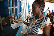 Keukeu Laito, 29, who is 5-month pregnant with her second child, picks up malaria prophylaxis from the pharmacy counter at the Libreville health center in Man, Cote d'Ivoire on Wednesday July 24, 2013.