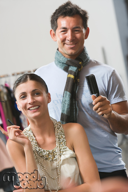 Mid adult woman in dressing room with hair stylist