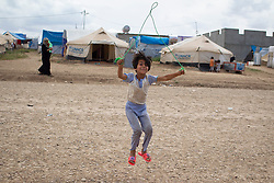 © Licensed to London News Pictures. 12/05/2013. Dohuk, Iraq. A young Syrian refugee skips with a piece of rope at a refugee camp inside Iraqi-Kurdistan set up for Syrians fleeing the ongoing civil war. The camp, close to the city of Dohuk, now houses in the region of 45,000 refugees, with around 400 new arrivals every day. Photo credit: Matt Cetti-Roberts/LNP
